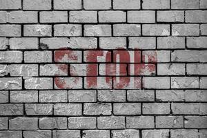 stop dipinto su un muro di mattoni