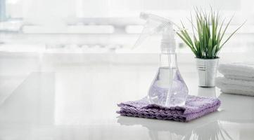 flacone spray e asciugamano sul tavolo bianco in cucina