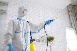 uno staff medico in tuta protettiva sta usando spray disinfettante in soggiorno,