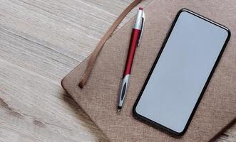 mockup di smartphone su una borsa con una penna