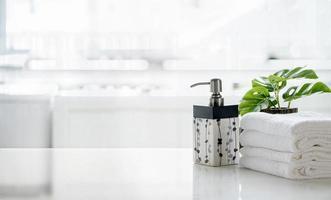 bottiglia di sapone con asciugamani e una pianta su un tavolo
