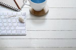 caffè e tastiera su una scrivania in legno