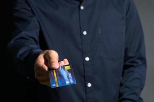 un uomo d'affari che mostra la carta di credito
