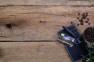 carta di credito con libro e chicchi di caffè foto