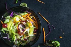insalata di verdure su sfondo nero foto