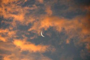 luna che appare dietro le nuvole arancioni foto