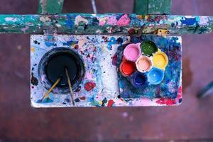 vista dall'alto di una tavolozza di colori e pennelli