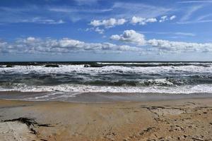 onde che si infrangono sulla spiaggia foto