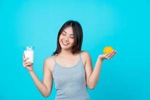 giovane donna asiatica con in mano un bicchiere di latte e un'arancia