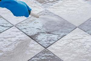 primo piano di una persona che spruzza un pavimento di piastrelle con acqua foto