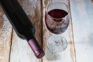 bicchiere di vino e bottiglia di vino sulla tavola di legno