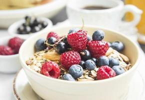 muesli con lampone, mirtillo e ribes, caffè e succo di frutta foto