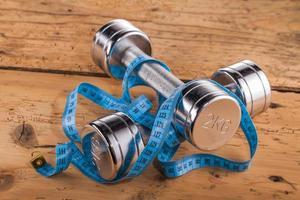 attrezzature per il fitness e metro a nastro sul tavolo di legno foto