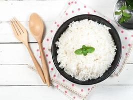 ciotola piena di riso e cucchiaio su sfondo bianco foto