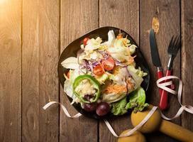 manubri, metro a nastro e insalata di cibo sano su backgrou in legno foto