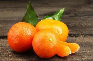 mandarini con foglie sul tavolo grigio in legno