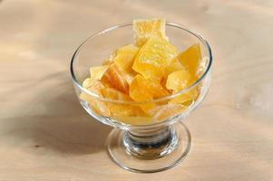 pezzi dolci secchi di mango in una ciotola su una superficie di legno foto