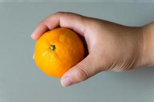 frutta arancione tenuta a mano