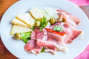 piatto di specialità gastronomiche con formaggio prosciutto e olive foto