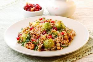 un piatto pieno di insalata tiepida di grano saraceno con cavoletti di Bruxelles foto