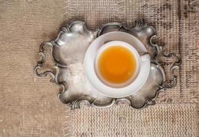 primo piano della tazza di tè su sfondo tessile vintage foto