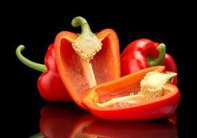closeup peperoni rossi a fette isolati su fondo nero foto