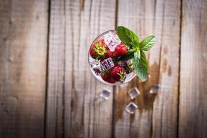 fragole fresche con menta in un bicchiere sul tavolo di legno