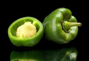 closeup peperoni verdi divisi in due isolati su fondo nero foto