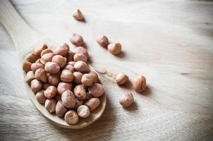 primo piano delle arachidi sul mestolo di legno foto