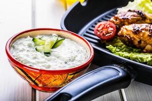 Salsa greca Tzatziki. condimento tzatziki. salsa tzatziki con cosce di pollo grigliate foto