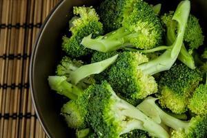 mazzo di broccoli verdi freschi nella ciotola su sfondo di legno foto