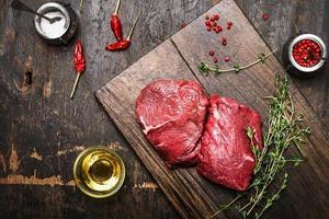 bistecche di carne su tagliere rustico con timo e spezie foto