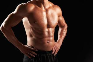 costruttore di corpo maschile a torso nudo con le mani sui fianchi, raccolto foto