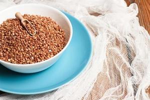 grano saraceno in una ciotola su un tavolo di legno foto