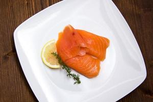 salmone affumicato sulla piastra su legno dall'alto foto