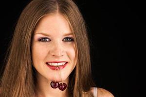 donna felice con ciliegie su bianco foto
