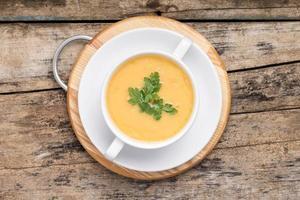 zuppa di piselli in una ciotola bianca su sfondo legno grunge. foto