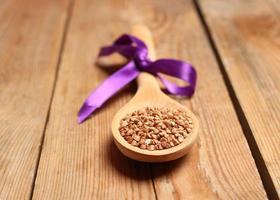 grano saraceno in un cucchiaio su un tavolo di legno foto