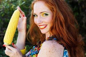 ragazza sorridente con le lentiggini che tengono pannocchia di mais foto