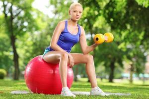 giovane donna che si esercita con una palla di manubri e pilates foto