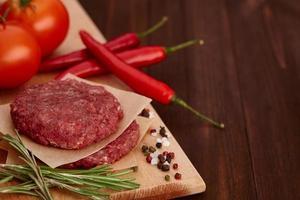 carne cruda per hamburger con spezie su tavola di legno