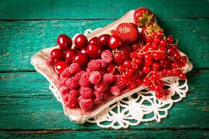 bacche fresche estive, fondo in legno, cibo sano. foto