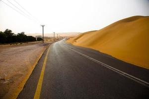 tortuosa strada e dune di sabbia a liwa, emirati arabi uniti foto