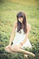 bella giovane donna con musica d'ascolto del vestito bianco foto