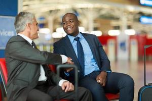 handshake di viaggiatori d'affari in aeroporto foto