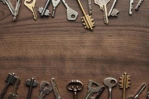 molte chiavi diverse sul tavolo di legno foto