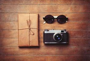 fotocamera vintage e occhiali da sole con pacchetto