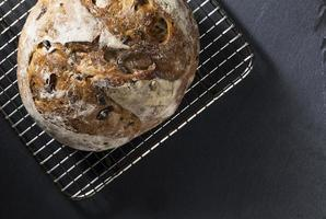 pagnotta di pane rotondo sul bordo di ardesia nera.