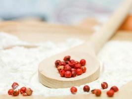 peperone rosso posto su un cucchiaio di legno foto