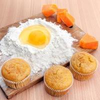 cupcakes, farina e uova sul tavolo della cucina foto